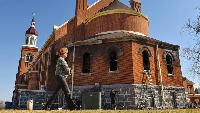 Deb Streese, Sauk Centre, walked around the Church of St. Mary on Saturday, March 12, to see the damaged caused by fire Friday night to the church in Melrose.