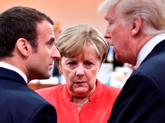 Angela Merkel stands between President Trump and Emmanuel