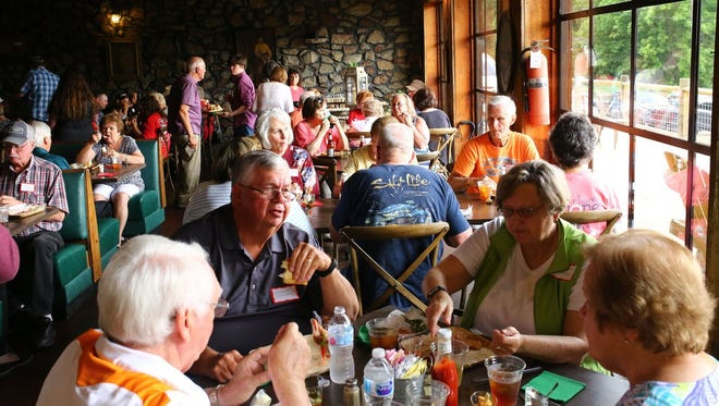 Customers eat at tables overlooking the Tennessee River at the Catfish Hotel.