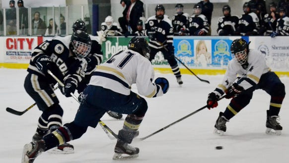Will Dodge (15) fires the puck between two defenders
