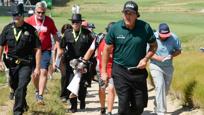 Phil Mickelson leaves the course Saturday after carding an 81 that included a 10 on the 13th hole.