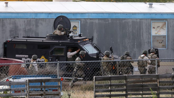 Members of the Farmington police SWAT team approach a home on Wednesday in the Lee Acres subdivision east of Farmington.