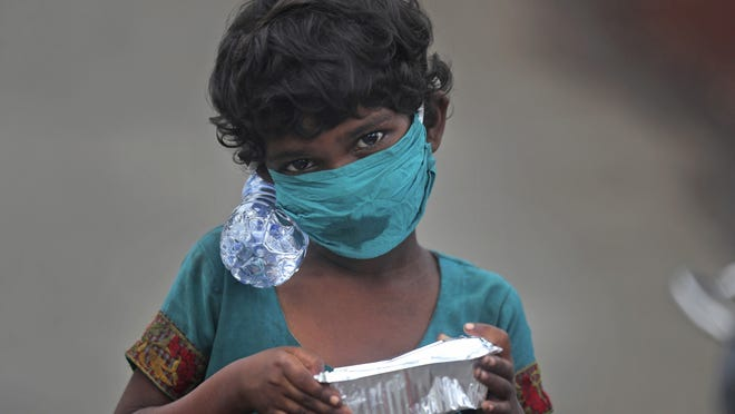 A girl wearing a face mask walks with a bottle of drinking water and a food packet that she received from a food distribution site in Mumbai, India, Saturday.