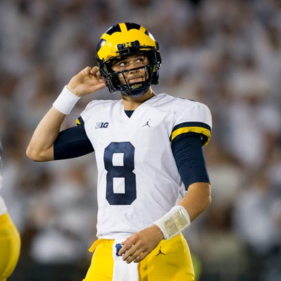 Michigan quarterback John O'Korn walks off the field