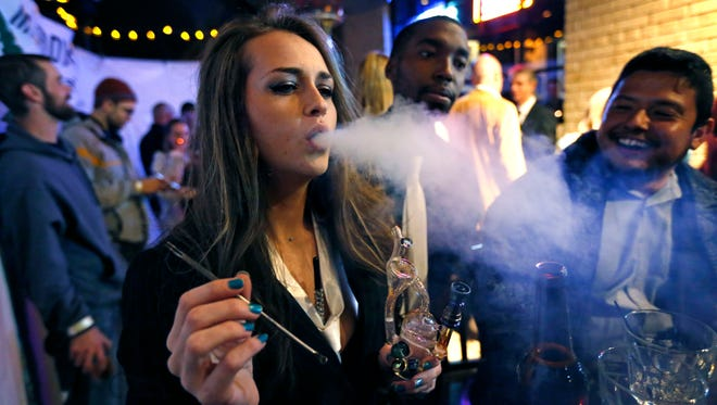 A woman smokes marijuana during a Prohibition-era themed New Year's Eve party at a bar Dec. 31, 2013, in Denver, the day before Colorado allowed retail sales of marijuana to those 21 and older.