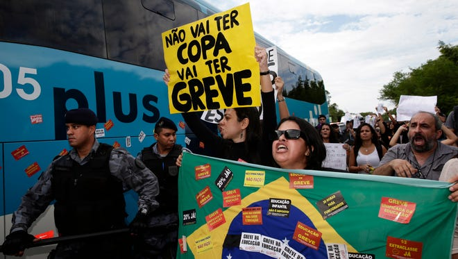 """Protesters shout next to a bus carrying some members of Brazil's national team The sign reads in Portuguese """"There will be not Cup. There will be a strike."""""""
