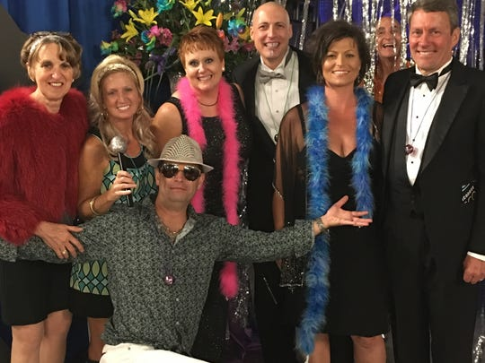 There were lots of laughing and photos during the Party of the Year. Pictured kneeling is Dr. Todd Burry; behind is Linda White, Amanda Burry, Jane and Dr. Matt Vassy and Misty and Dr. Bruce Adye. Peeking out from the back is Ron Rhodes.