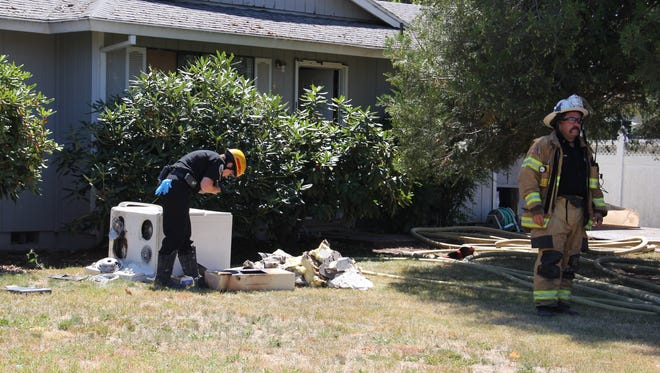 Investigators examine an oven damaged in a fire at a northeast Salem home Thursday.