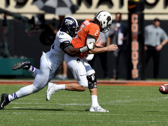 FILE - In this Sept. 23, 2017, file photo, TCU defensive end Ben Banogu, left, forces a fumble by Oklahoma State quarterback Mason Rudolph during the first half of an NCAA college football game in Stillwater, Okla. The 6-foot-4, 240-pound Banogu leads TCU with four sacks and eight tackles for loss. (AP Photo/Brody Schmidt, File)
