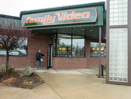 A patron returns a video at the Family Video, at the