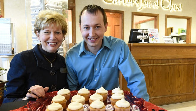 Beth Carter and her son, Chris, display a tray of carat cakes that will be available for $5 Friday and Saturday at Carter's Jewel Chest to benefit Christmas Wish. Each cupcake contains a special prize, one of which is a diamond. This is the 23rd year the Carter family has hosted this event.