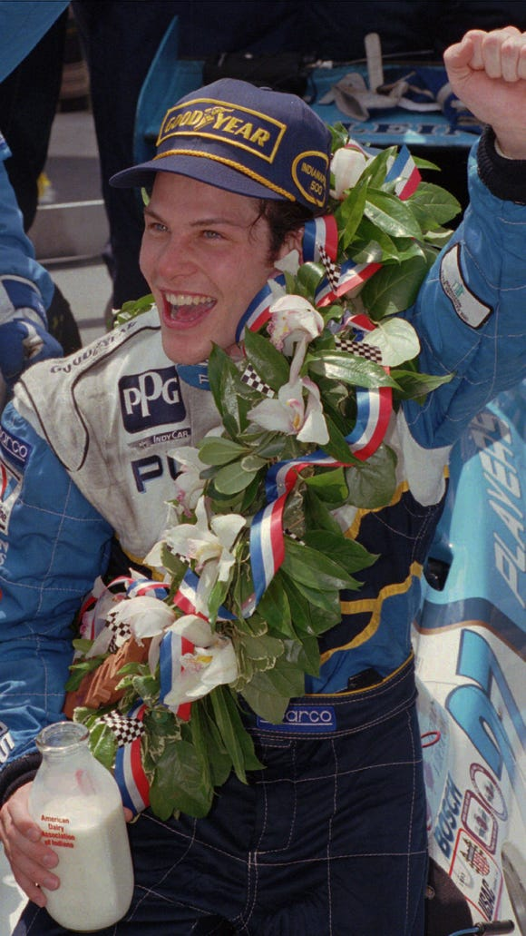 FILE--Jacques Villeneuve, of Canada, raises his fist while holding the winner's bottle of milk in victory lane after winning the Indianapolis 500 on May 28, 1995.