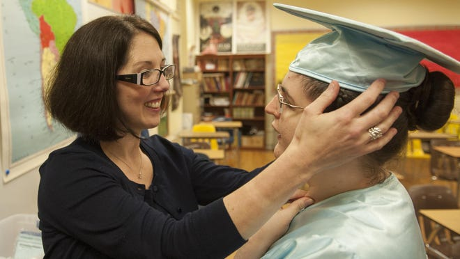 Laura Atkinson interacts with her daughter Casey before Bancroft's graduation ceremony at Haddonfield Memorial High School. The family moved to New Jersey so their daughter with special needs could go to Bancroft.
