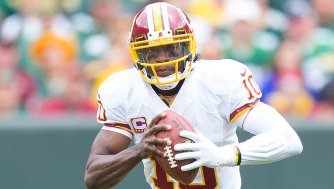 Washington Redskins quarterback Robert Griffin III (10) scrambles with the fooball during the second quarter against the Green Bay Packers at Lambeau Field.