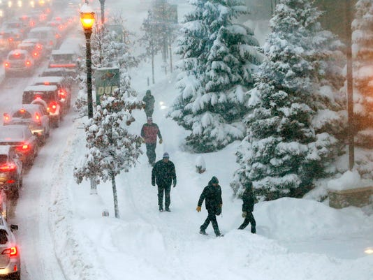 Backup traffic waits at a light as pedestrians arrive at Xcel Arena for a Minnesota Wild and Ottawa Senators NHL hockey game Monday, Jan. 22, 2018, in St. Paul, Minn. as heavy snow and strong winds are pushing through the Midwest. (AP Photo/Jim Mone)