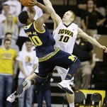 Michigan guard Derrick Walton Jr. shoots over Iowa guard Mike Gesell, right, during the second half Sunday.