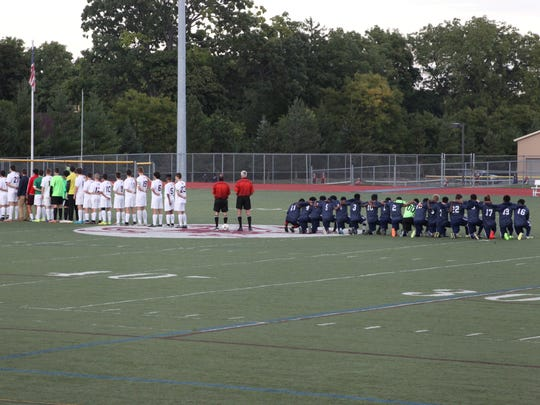 In this file photo, School 58/World of Inquiry boys soccer players kneel during the national anthem prior to their game with Aquinas.