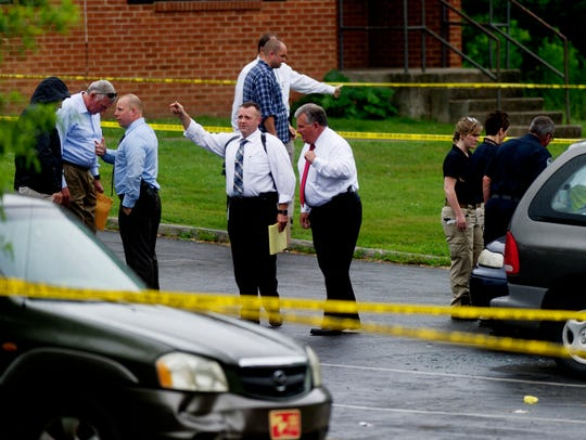 Police investigate at the scene of a triple shooting