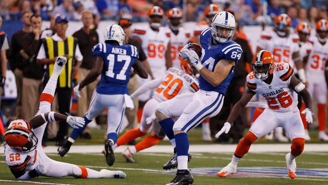 Indianapolis Colts tight end Jack Doyle (84) catches a pass and spins around to avoid a tackle by the Cleveland Browns at Lucas Oil Stadium.