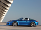 The 2014 Porsche Targa resembles the 1965 classic with its distinctive roof bar, but the roof segment opens and closes with the touch of a button. Prices will begin under $102,000 this summer.