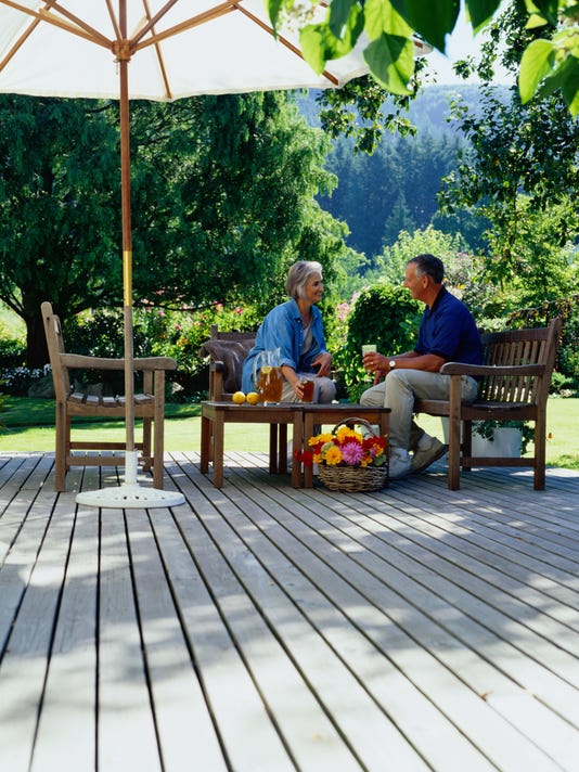 Mature couple sitting on outdoor deck drinking iced tea
