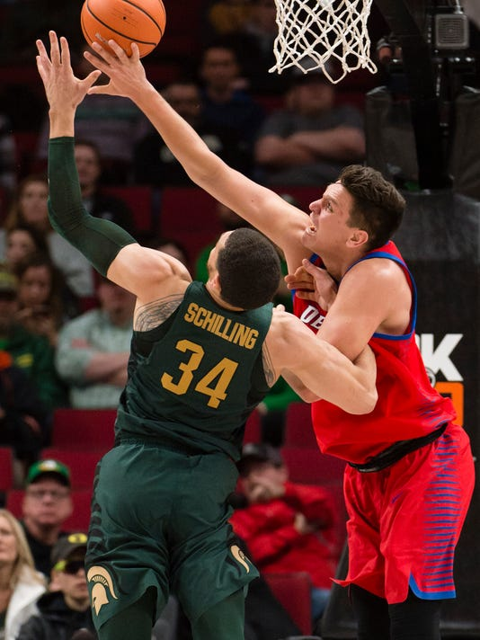 DePaul center Marin Maric, right, blocks a shot by Michigan State forward Gavin Schilling during the first half in an NCAA college basketball game at the Phil Knight Invitational in Portland, Ore., Thursday Nov. 23, 2017. (AP Photo/Troy Wayrynen)