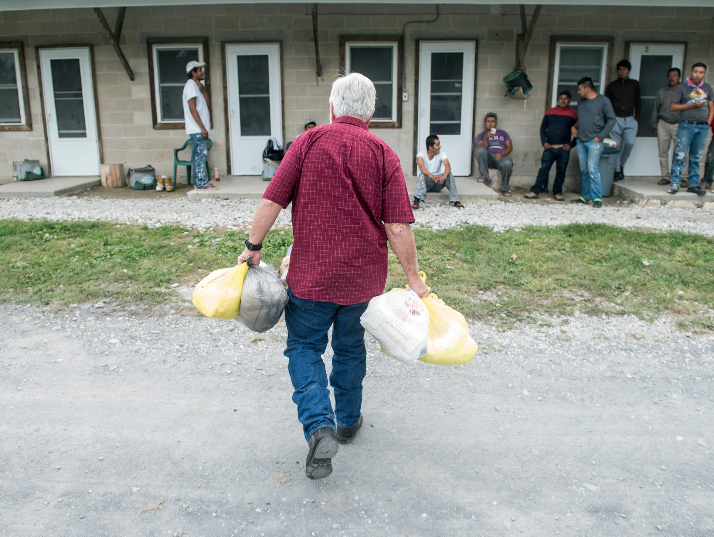 Reverend Roddy Runyan walks bags of toiletries to migrant