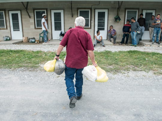 Reverend Roddy Runyan walks bags of toiletries to migrant workers, Monday, August 28, 2017. Fruitbelt Farmworker Christian Ministry provides items to migrant workers, from sweatshirts to toiletries to bibles. Reverend Roddy Runyan has been making rounds to help migrant workers since 1990.