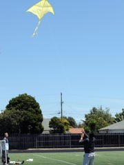 Palma sophomore Pedro Gomez flies a kite with teammate Dominic Turturici (not shown) on Monday. The kite is handmade and inscribed with sayings from The Kite Runner, by Khaled Hosseini.