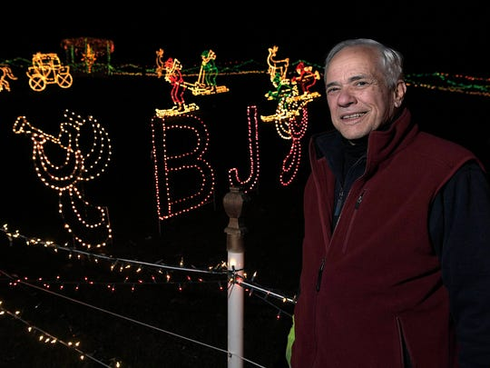 """Bill Minneci stands next to his son's name in lights.  BJ, who died in 1993, is remembered by Minneci with """"Sunnyside Lights,"""" a beloved holiday light display in Brentwood's Sunnyside subdivision.   After 35 years, Minneci says his holiday lights display will end. The legendary display was started in memory of Minneci's son, BJ."""