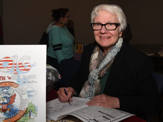 Cartoonist Kate Salley Palmer of Clemson colors in a copy of her new adult coloring book on the 2016 presidential candidates at the Pickens County Library in Easley.
