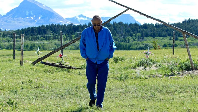 Dale Ell pauses at his family cemetery outside of Browning on the Blackfeet Indian Reservation. His Uncle, George Ell, will be reburied there Saturday after a 128-year absence.