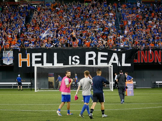 "Fans drop a ""Hell is Real"" banner, referring to a series of billboards on I-71 between Cincinnati and Columbus after the US Open Cup soccer match between FC Cincinnati and Columbus Crew at at Nippert Stadium on June 14, 2017."