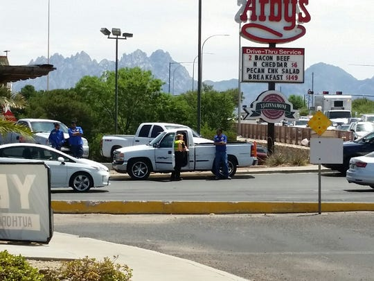 Authorities inspect a white truck that crashed into a pedestrian while turning onto Walton Boulevard in Las Cruces on Tuesday, July 3, 2018. Police say the driver of the truck is believed to have had a green arrow at the time of the crash.