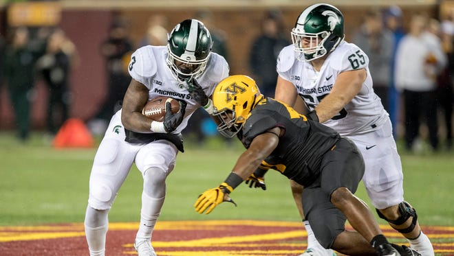 Michigan State Spartans running back LJ Scott (3) rushes for a first down as Minnesota Golden Gophers linebacker Thomas Barber (41) makes a tackle in first half at TCF Bank Stadium.