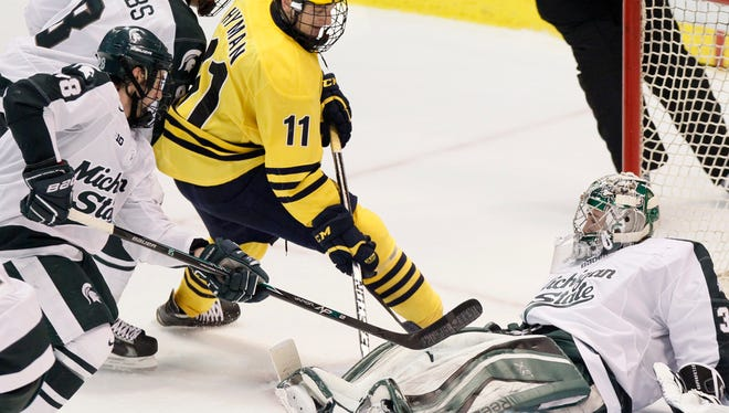 Michigan State goalie Jake Hildebrand (30) stops a shot by Michigan's Zach Hyman (11) as Michigan State's Thomas Ebbing (28) and Josh Jacobs (8) help defend the goal during the third period of the Great Lakes Invitational championship game Monday, Dec. 29, 2014, in Detroit. Michigan won the championship 2-1.