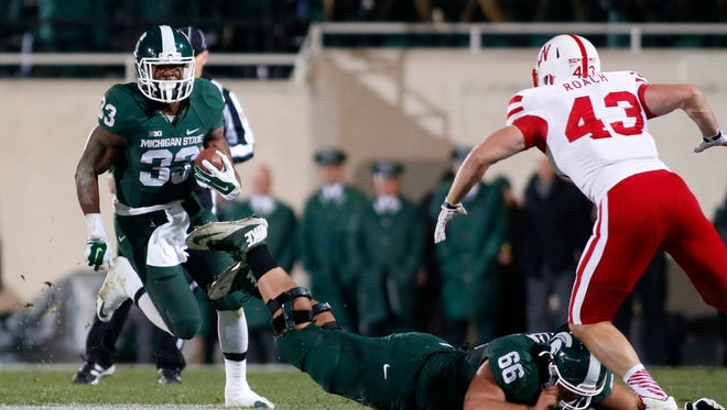 Michigan State's Jeremy Langford (33) rushes against Nebraska's Trevor Roach (43) as Michigan State's Jack Allen (66) tries to block during the first quarter of an NCAA college football game, Saturday, Oct. 4, 2014, in East Lansing, Mich.