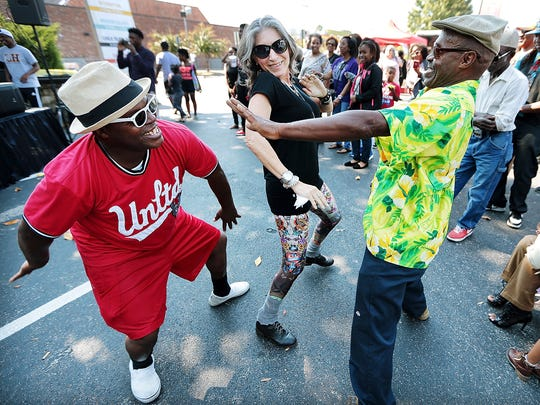Ronald Terry Box (left) and his brother Donald Perry Box (right) dance with Rubia Carneiro of Brazil as the band Interruption performs at the Soulsville USA Festival behind the Stax Museum of American Soul Music.
