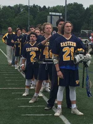 Senior attacker Dom Particelli (21) and the rest of the Eastern York boys' lacrosse team line up for the National Anthem ahead of the District 3 2-A semifinal game against Palmyra.