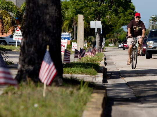 Hundreds of American flags line the right of way Monday on 47th Terrace between Coronado Parkway and Country Club Boulevard in Cape Coral, the apparent culmination in a fight between Jeffrey Verzi and the city's code enforcement authorities.