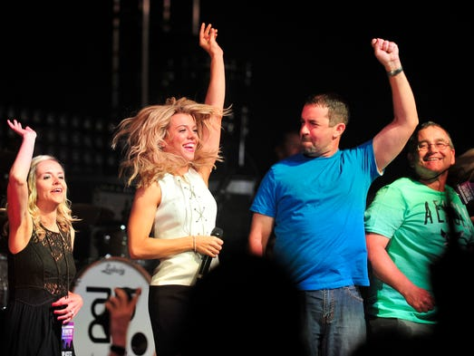 Kimberly Perry of The Band Perry dances with fans on stage at the Fan Club Party during the 2014 CMA Music Festival at Music City Center.