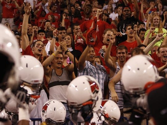 FILE – Ball State fans cheer as Cardinals players greet them in the stands after beating Indiana at Lucas Oil Stadium, Sept. 3, 2011.