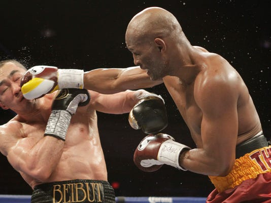 Beibut Shumenov, left, of Kazakhstan, takes a punch from Bernard Hopkins, right, of the United States, during their IBF, WBA and IBA Light Heavyweight World Championship unification boxing match, Saturday, April 19, 2014, in Washington. Hopkins won by a split decision. (AP Photo/Luis M. Alvarez)
