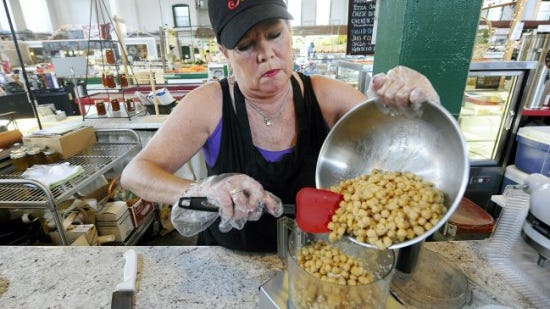 Cheryl Ness, co-owner of Saucy Girls, pours chickpeas into a mixer while making hummus at her stand at Central Market on Thursday. (Jason Plotkin - York Daily Record/Sunday News)