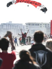 Spectators watch as skydivers dressed as Santa and his helpers land on the beach at the Cocoa Beach Pier during a previous Skydiving Santas event in Cocoa Beach.
