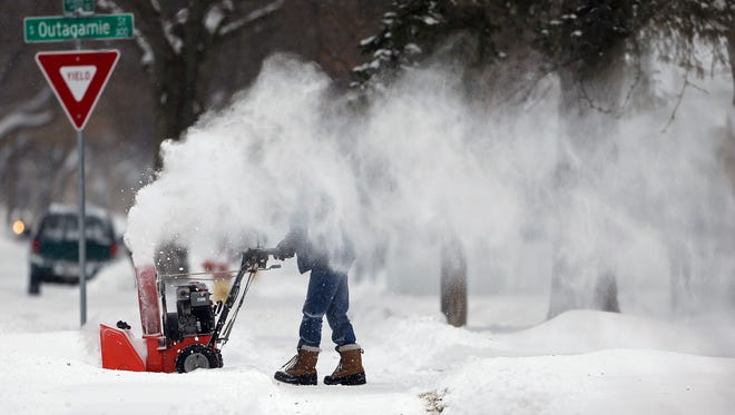 Eric Miron is hidden by blowing snow helped along by a brisk wind as he clears a driveway Sunday, February 4, 2018, in Appleton, Wis.Ron Page/USA TODAY Network-Wisconsin