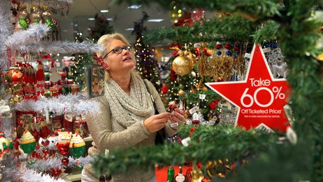 Julie Kuehner shops for ornaments for her grandchildren at Macy's in the St. Louis, Mo., Galleria on Tuesday, Dec. 23, 2014.