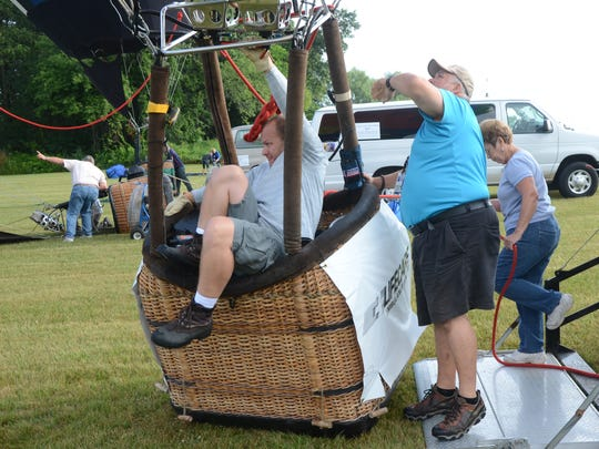 Jeff Pestun of Holland climbs backwards into his basket as he inflates his balloon Monday.