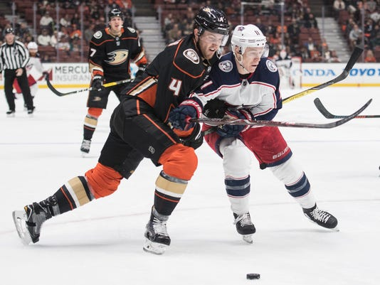 Anaheim Ducks defenseman Cam Fowler, left, and Columbus Blue Jackets left wing Matt Calvert battle for the puck during the first period of an NHL hockey game in Anaheim, Calif., Friday, March 2, 2018. (AP Photo/Kyusung Gong)