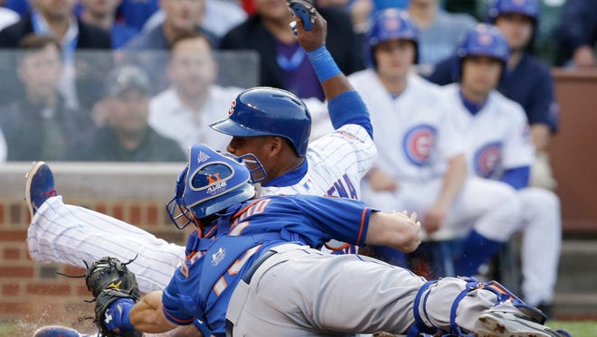 The Chicago Cubs' Luis Valbuena, top, scores on a sacrifice fly as Mets catcher Travis d'Arnaud tries for the tag during the second inning.